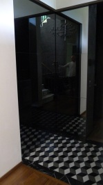 """This entry, featuring a marble """"tumbling block"""" pattern, serves to re-orient the visitor into the alternate reality of this house, and serves as a formal de-cloaking room, with full closet behind the mirror door."""
